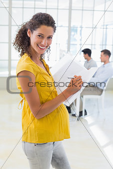 Casual pregnant businesswoman writing in folder smiling at camera