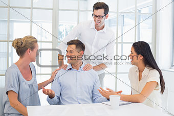 Casual business team sitting at desk talking