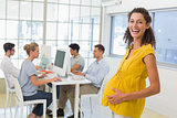Casual pregnant businesswoman smiling at camera