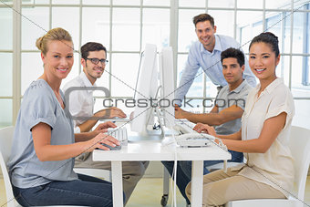 Casual business team smiling at camera at desk