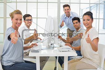 Casual business team smiling at camera showing thumbs up