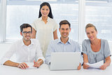Casual business team working together at desk smiling at camera