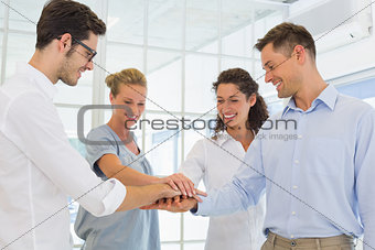 Casual business team putting their hands together