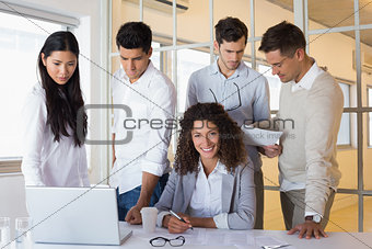 Casual business team having a meeting with woman smiling at camera