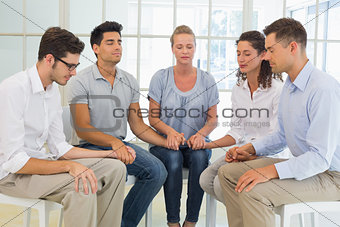 Group therapy in session sitting in a circle holding hands