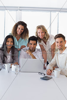 Casual smiling business team having a meeting using laptop