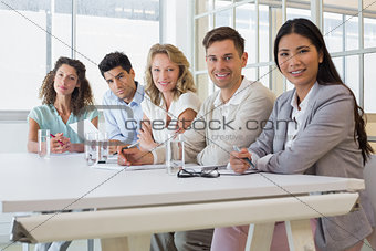 Casual business team smiling at camera during meeting