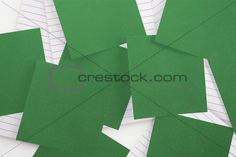 Green paper strewn over notepad