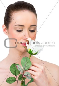 Beautiful brunette smelling white rose