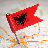 Albania Small Flag on a Map Background.