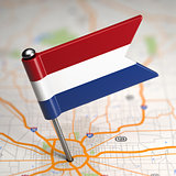 Netherlands Small Flag on a Map Background.