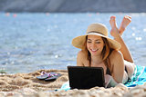 Woman on the beach browsing social media on a computer in summer