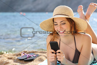 Woman on the beach texting a smart phone in summer