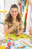Smiling young woman making easter decoration