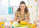 Happy young woman making easter decoration in studio