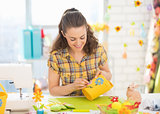 Happy young woman making easter basket in studio