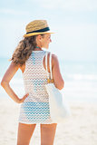 Relaxed young woman in hat with bag on beach looking into distan