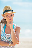 Portrait of thoughtful young woman in hat on beach