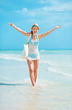 Young woman in hat with bag walking on sea coast and rejoicing