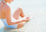 Closeup on young woman in swimsuit sitting on sea shore and play