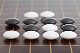 stones during go game playing on wooden board