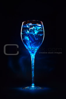 Amazing blue cocktail with ice cubes on dark background. Magic l