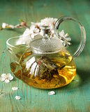 glass teapot with exotic green tea on a wooden table