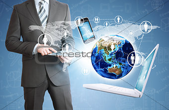 Man holding tablet. Near the earth and electronics