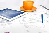 Tablet pc, orange cup and paper with graphs