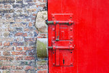 Red painted door with locks and brickwork