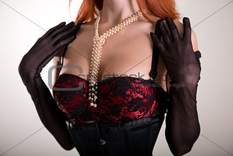 Close-up shot of a busty redhead woman in vintage red bra and sh