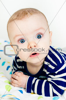 cute baby in striped clothes lying down on a blanket