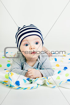cute baby in striped hat lying down on a blanket
