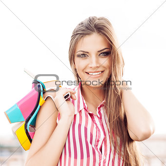 beautiful woman in sleeveless striped top holding bright high he