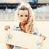beautiful young lady with a skateboard with blank deck