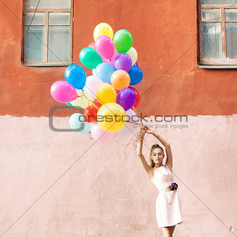 beautiful lady in retro outfit holding a bunch of balloons betwe