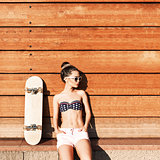 beautiful sexy girl with skateboard poses against wooden wall