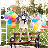 beautiful lady in retro outfit holding a bunch of balloons in ci