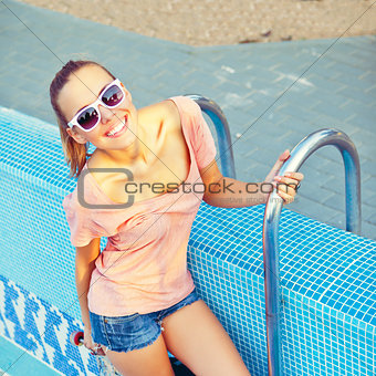 a beautiful young girl with a scateboard on the pool ladder