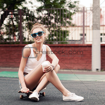 beautiful sexy lady in jeans shorts with skateboard and to-go cu