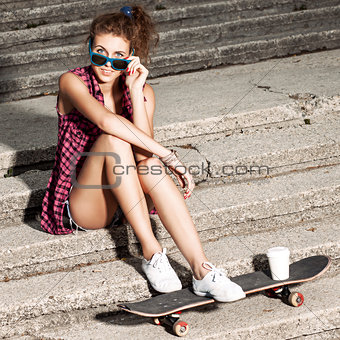 beautiful sexy lady in jeans shorts with skateboard at stone sta