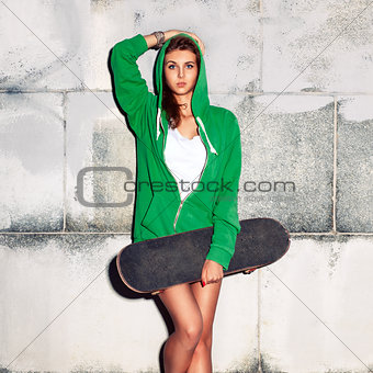 beautiful sexy lady in jeans shorts with skateboard against  gre