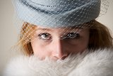 Redhead close-up in blue veiled hat and fur