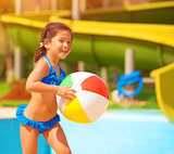 Little girl with ball near pool