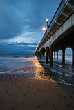 Twilight dusk landscape of pier stretching out into sea with moo