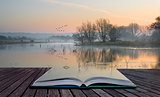 Book concept Landscape of lake in mist with sun glow at sunrise