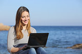 Happy teenager girl browsing social media on the beach