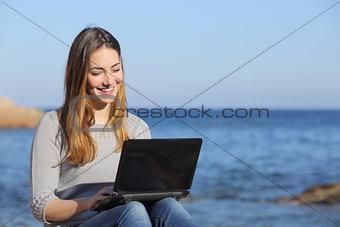 Happy teenager girl browsing social media on the beach
