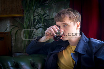 Young man holding a glass of pink wine in the restaurant