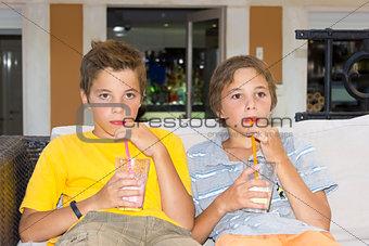 Adorable boys with glasses of milkshake